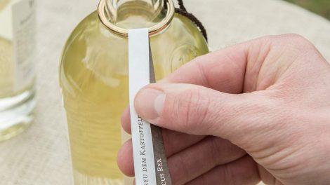 Auch das Fähnchen am stylishen Goldring (damit der Korken nicht verloren geht) wird in Hand angelegt. Quelle: windspiel-gin.de