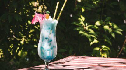 Ein sommerlicher Swimming Pool Cocktail mit Schirmchen und Rühr-Ananas.
