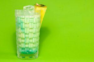 Der Swimming Pool im Longdrink-Glas sieht stilvoller aus als die Fancy-Drink-Variante. Auch auf einer giftgrünen Wiese aus Papier.