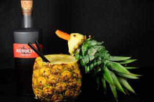 Revolte Overproof Rum in einer Pina Colada, serviert in einer Ananas, garniert mit einem Ananas-Schnabeltier.