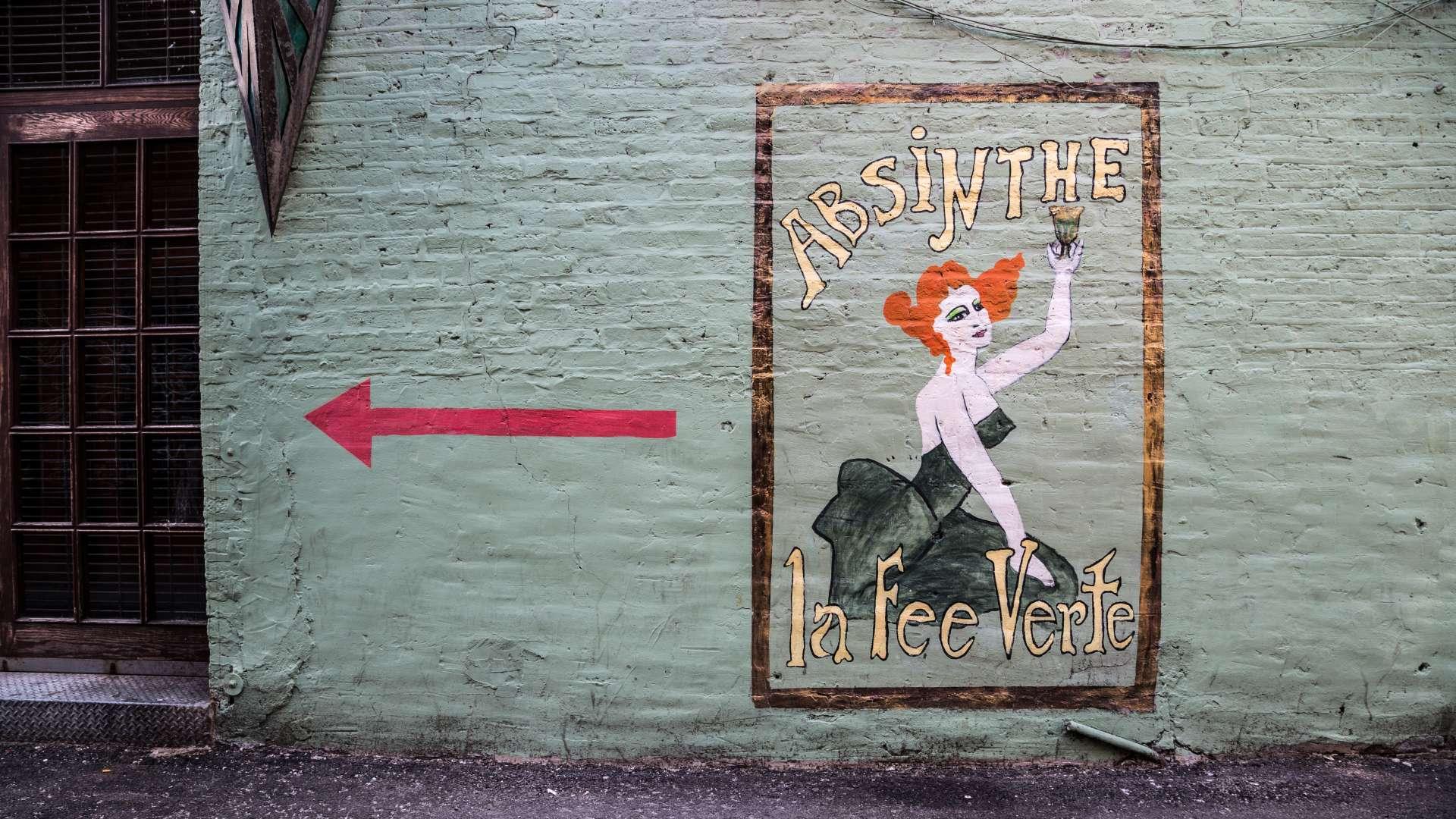 Ein Schild, das zu einer Absinth-Bar führt.