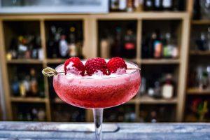 Der Clover Club Cocktail, garniert mit frischen Himbeeren.