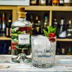 Rubus Gin in einem Gin Tonic garniert mit Minze und Himbeeren.