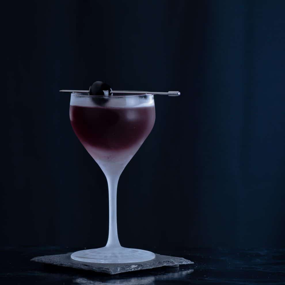 Ein Manhattan Cocktail mit Rye Whiskey, Wermut und einer Maraschino-Kirsche.