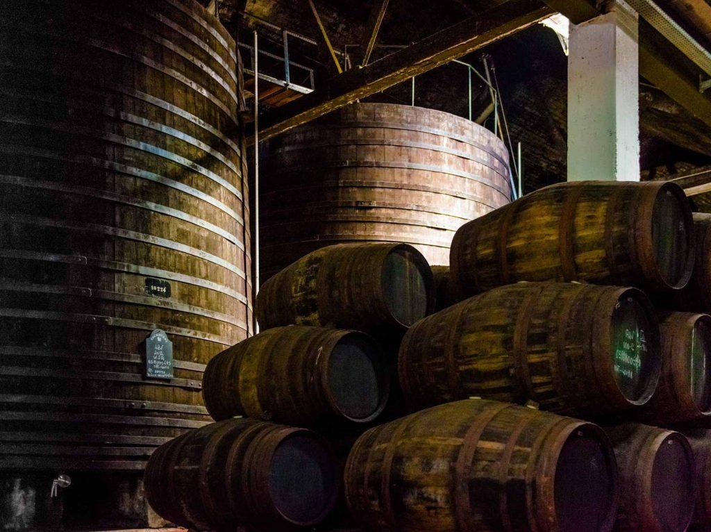 Im Hintergrund sieht man die großen Holzbottiche, in denen alle Portweine mindestens zwei Jahre lagern. Die Port Pips im Vordergrund kommen nur bei Tawnys zum Einsatz.