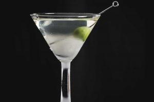 Ein trockener Martini, garniert mit einer einzelnen Olive.