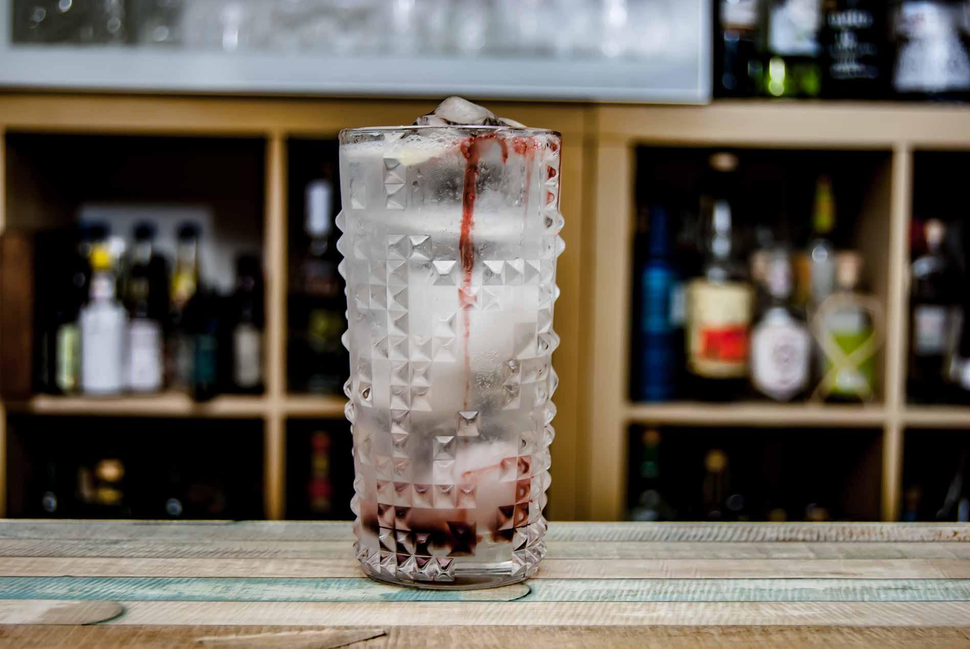 Ein klassischer Gin Fizz mit einer Marschinokirsche nebst Saft als Garnitur.