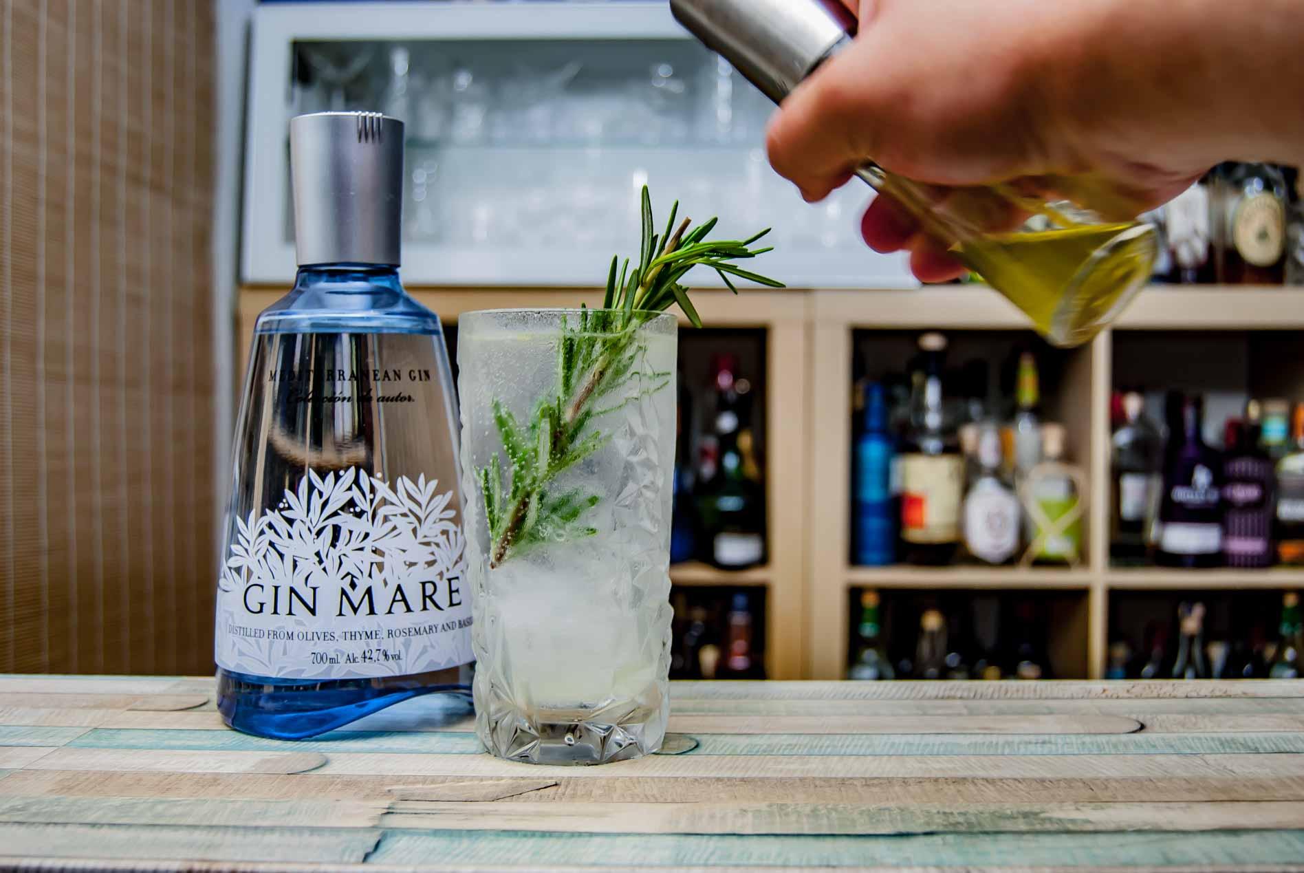 Ein mediterraner Gin Fizz (Flasche an anderer Stelle gesponsert vom Hersteller) mit einem Rosmarinzweig und einem Sprühstoß Olivenöl als Deko.