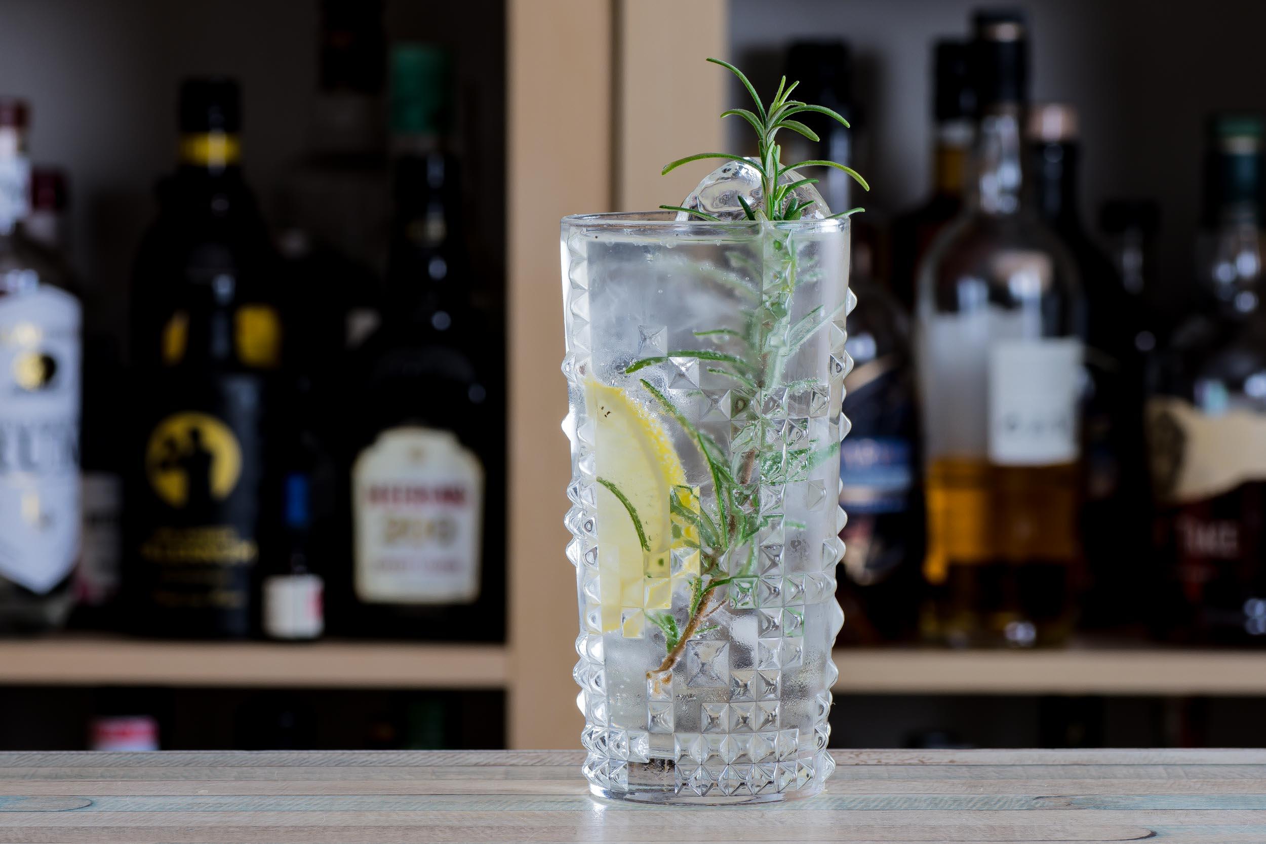 Ein Gin Tonic mit Rosmarin und Zitrone.