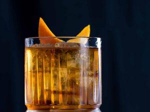 Ein Old Fashioned Cocktail mit Bourbon Whiskey, Bitters, Zuckersirup und Orangenzeste.