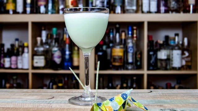 Ein Grasshopper Cocktail mit Origami-Grashüpfer.
