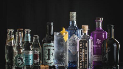 Fünf Flaschen Gin, fünf Flaschen Tonic Water und ein Gin Tonic.
