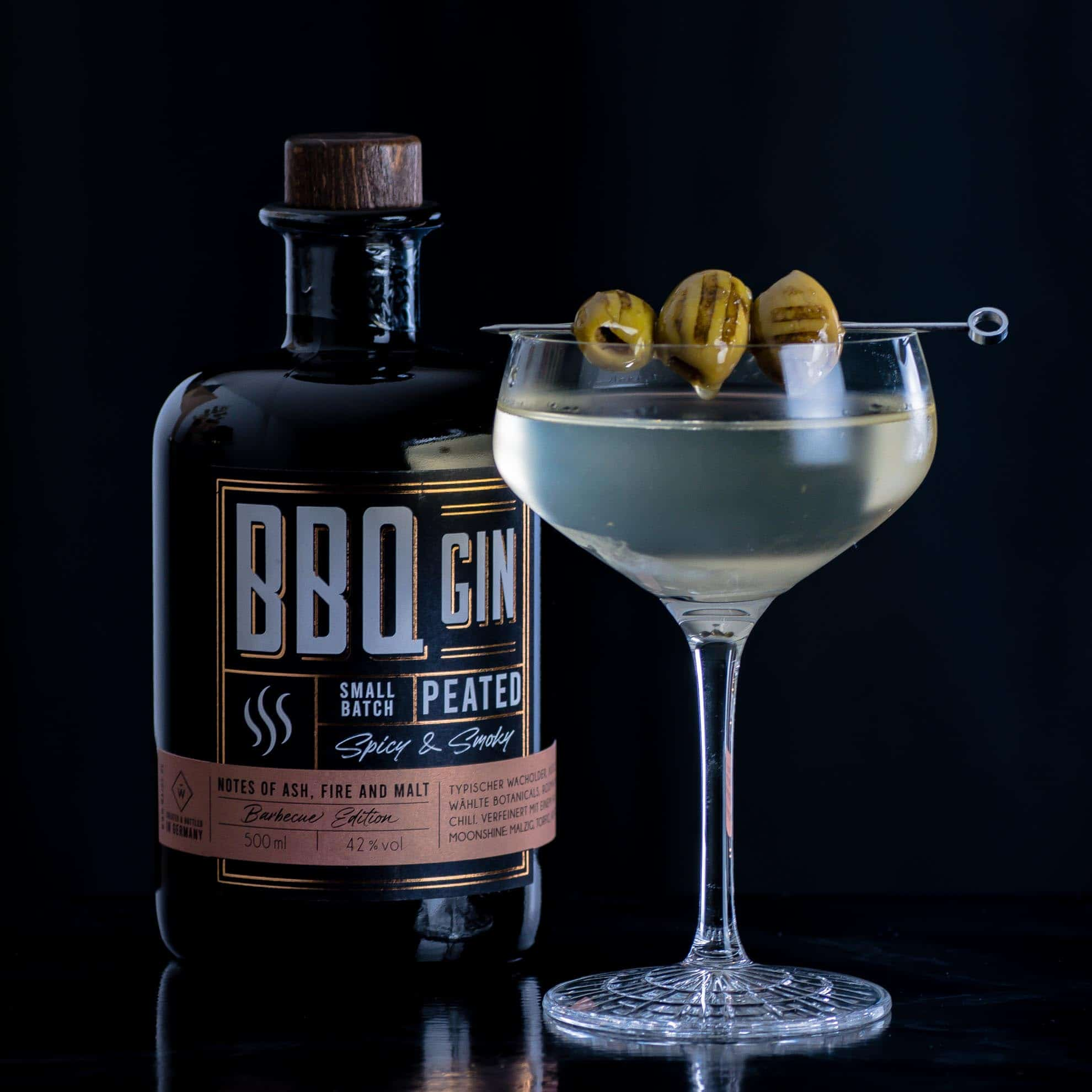 Wajos BBQ Gin in einem Martini mit gegrillten Oliven.